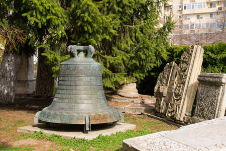 Bucharest, Romania - March 16, 2019: big bronze church bell situated in the courtyard of Church