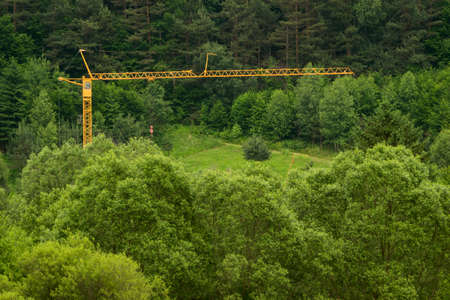 big yellow construction crane installed in the middle of the green forest Reklamní fotografie