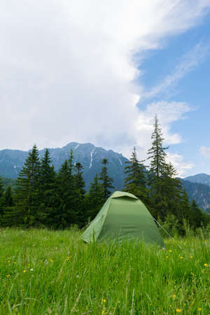 one green tent installed in the wild mountain scenery