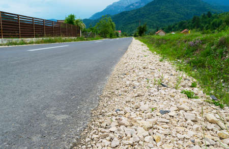 asphalt road with gravel on the side leading to the mountains in the far background Reklamní fotografie
