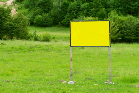 Blank billboard with green grass and trees in the background Reklamní fotografie
