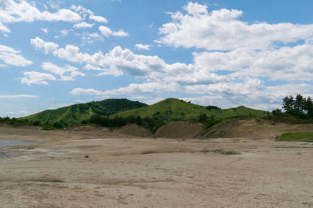 contrast between arid soil in the foreground and green hills in the background with beautiful blue sky