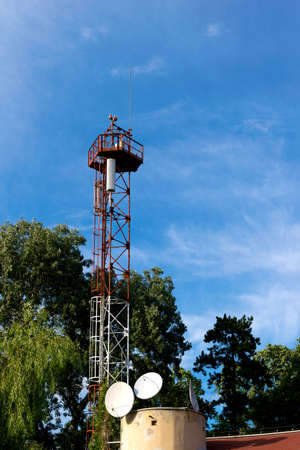 metal tower with GSM antenna surrounded by green trees - copyspace