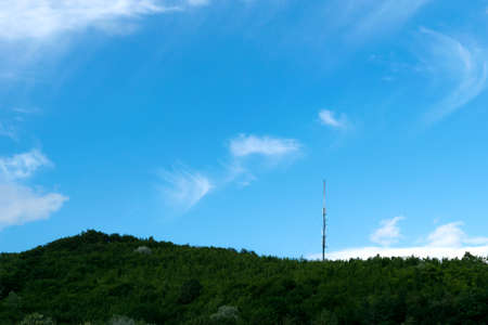 metal tower with GSM antenna on top of green forest hill - copyspace