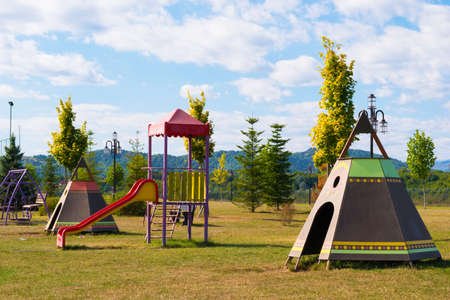 Empty children play park with slides and teepee tents