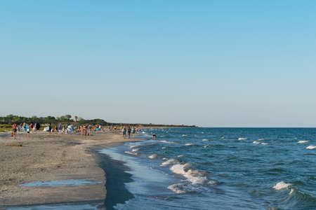 Corbu, Constanta, Romania - August 18, 2019: The beach in Corbu with tourists in the background, Romania.