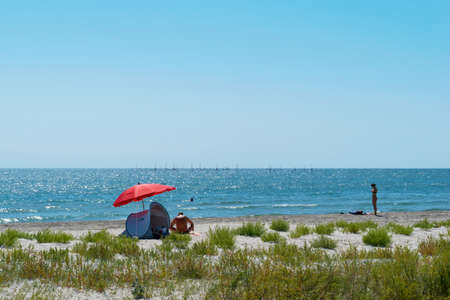 Corbu, Constanta, Romania - August 18, 2019: People enjoy a relaxing summer day on the remote last virging beach in Corbu, Romania.