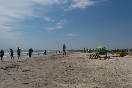 Corbu, Constanta, Romania - August 14, 2019: People enjoy a relaxing summer day on the last virging beach in Corbu, Romania.