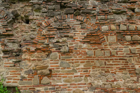 ancient deteriorated brick and stone wall background
