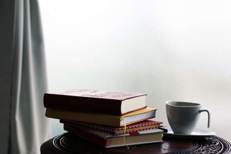 cappuccino cup: Pile of books lay on the round table and cup against light coming from the window
