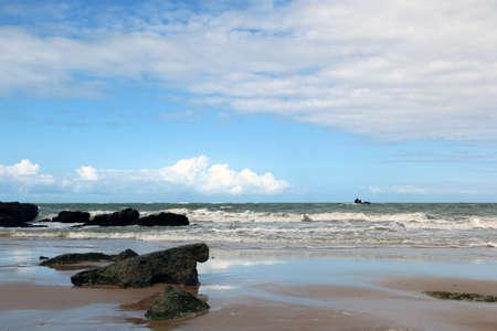 shoal: Black rocks in the shoal of ocean