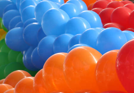 red balloons: Group of orange balloons followed by blue, red and green Stock Photo