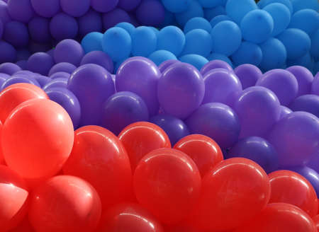 aligned: Bunch of red balloons followed by purple and blue