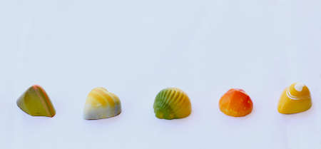 flavours: Chocolate bonbons with fruit flavours decorated with yellow, orange, green and white color Stock Photo