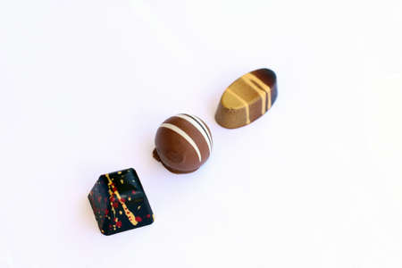 oval shape: Three chocolate bonbons in square, round and oval shape  in diagonal