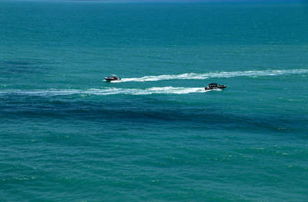 Two speedboats with passengers sail on deep perfectly blue sea in the opposite directions leaving a white trail behind