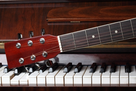 classical guitar: guitar neck on old piano keys Stock Photo