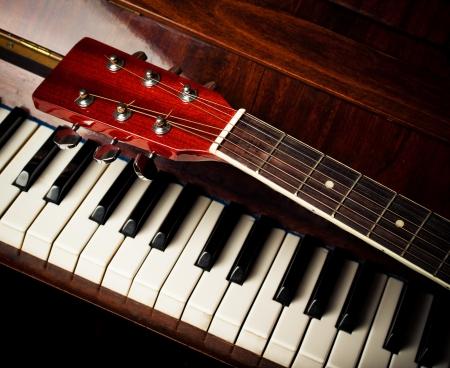 white piano: acoustic guitar neck on piano keys