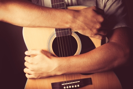 hands holding an acoustic guitar photo