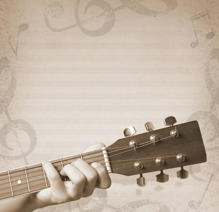 musical background with hand holding a guitar and musical notes photo