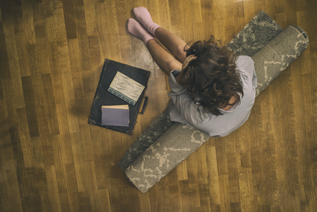 Beautiful young woman in a shirt on a rug with a suitcase. View from above. Stock Photo
