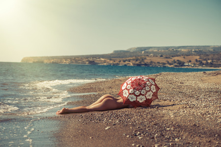 Beautiful naked girl lying on the beach under an umbrella. Against the backdrop of the rock Stock Photo