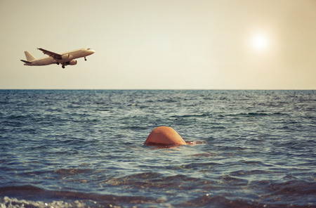 Young girl dives into the sea against the backdrop of the aircraft. Womens buttocks in seawater