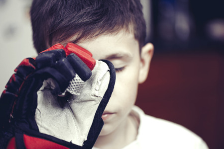 Little boy with hockey glove sad after loss. Sport concept Stock Photo