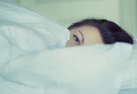A girl lies in bed can not fall asleep thinking and dreaming. Insomnia. Psychology.