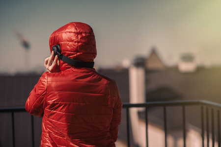 Beautiful girl in a red jacket and headphones. A girl on the balcony listening to music and singing Stock Photo