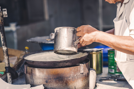A man is cooking a pie in the market of chinatown, Malaysia. Street food. 版權商用圖片