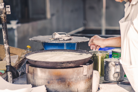 A man is cooking a pie in the market of chinatown, Malaysia. Street food. Stock Photo