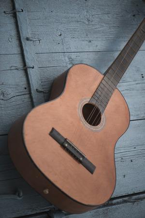 Brown antique guitar on a blue wooden door background