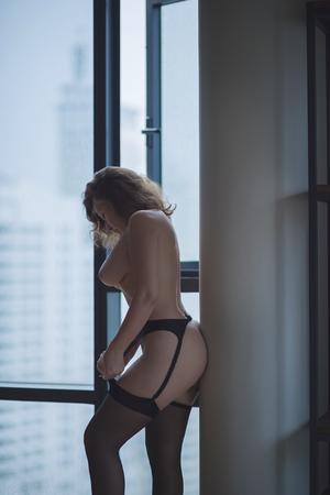 adult sex: Beautiful naked female putting stockings on the window background