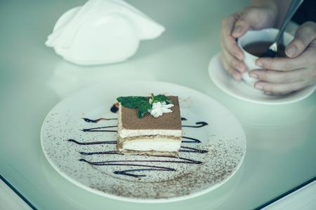 amaretto: Italian dessert tiramisu with mint with cup of tea on the table. Stock Photo