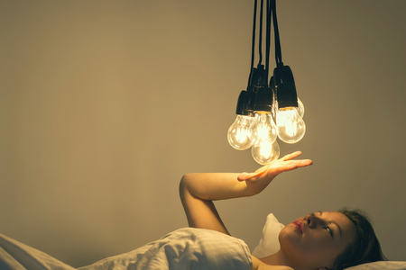 A girl lies in a bed under a big light bulbs. Concept picture. Insomnia. Psychology