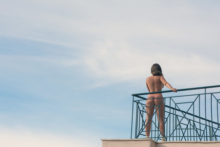 Naked female stands on the balcony 版權商用圖片