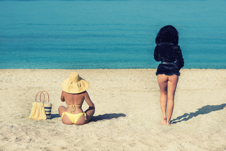 Female in a yellow swimsuit and a girl in a fur coat on the beach. Conceptual picture of winter and summer. Winter is leaving. Summer is leaving. Two seasons winter and summer.
