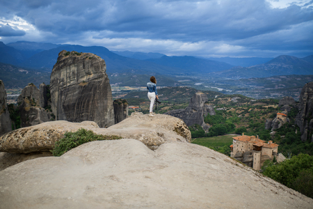 Alone female on the edge of the rock look on the monasteries of Meteora. Female on the rock and monasteries of Meteora in Greece in Thessaly at the early morning