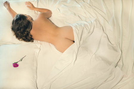 Beautiful naked female sleeping in bed. Flower on a pillow near a beautiful girl. View from above. A conceptual photo of the relationship between a man and a woman