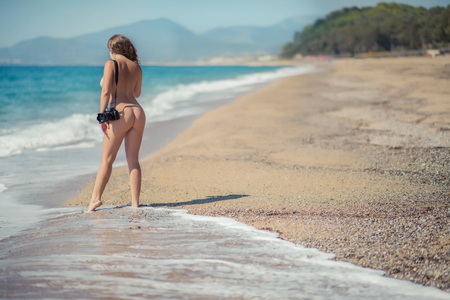 Beautiful female photographer with professional camera on the beach background. Naked female taking a picture in the sea wave