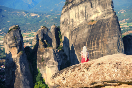 Alone girl in a red dress and scarf on the edge of the rock in Meteora. Creece in Thessaly. Pilgrimage in Greece