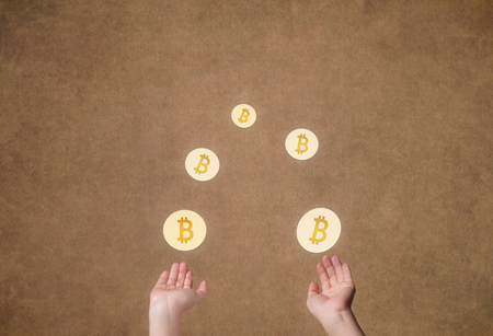 Female hands juggle of glowing coin crypto currency of bitcoin on gold background. Symbol BTC