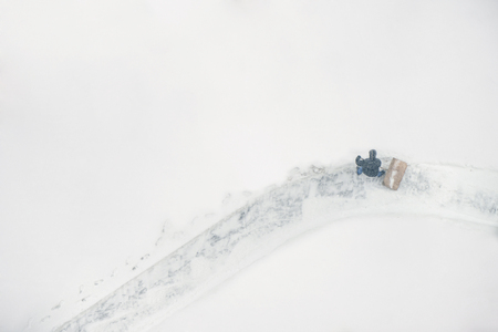 Janitor with a shovel cleans the snow in the courtyard. View from above Stock Photo