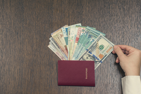 Travel passport and a bundle of Asian money on the table. A female hand takes one hundred US dollars banknote from bundle of Asia money 写真素材