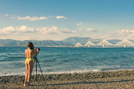 Young woman in the bikini on the beach with tripod and camera taking a picture of Rion-Antirion bridge near Patras, Greece