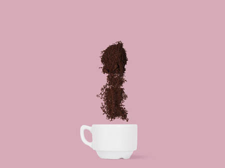 Coffee beans and ground coffee fall into the cup. Concept Banque d'images