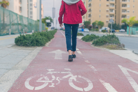 Unfocused boy's legs on the road for bicycle at dusk.  Bicycle sign on the road used for pedestrian crossing bicycle lane. Concept
