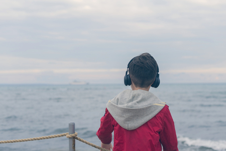 A boy in a red jacket and headphones looks at the sea waves in stormy rainy weather