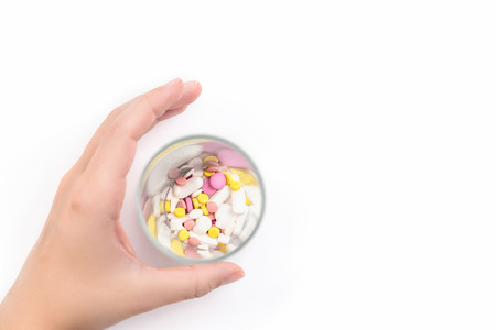 Female hand and glass full of colorful medicines,pills, vitamins or supplements. The concept of addiction treatment Stockfoto